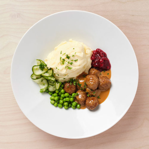 Meatballs with mashed potatoes, cream sauce, peas, lingonberry jam and pickled cucumber.