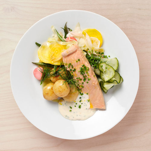 Cold-poached fillet of salmon with fermented vegetables, boiled potatoes, creamy egg sauce and pickled cucumber.